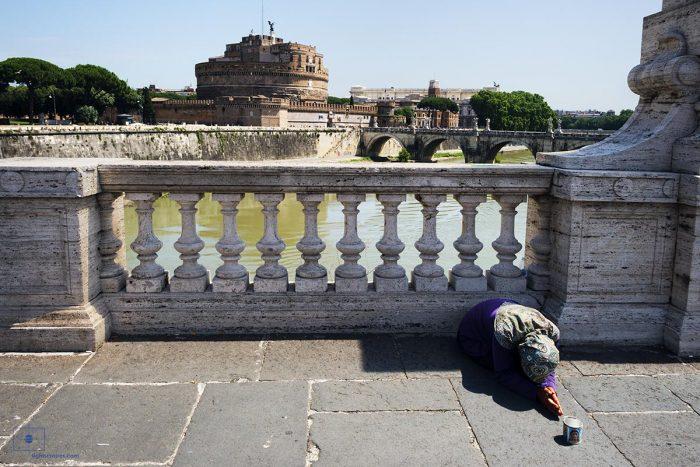 Mendicant on Ponte Vittorio Emanuele II and Tiber River, Rome Italy