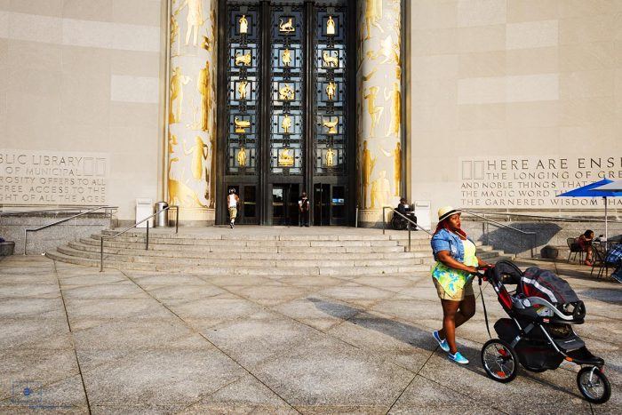 Mother with stroll in front of the Brooklyn Library in Grand Army Plaza, Brooklyn, New York