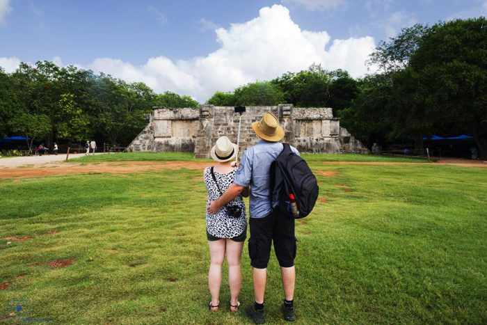 Couple Taking a Picture Using a Selfie Stick in Front of the Venus Platform, Chichen Itza, Mexico
