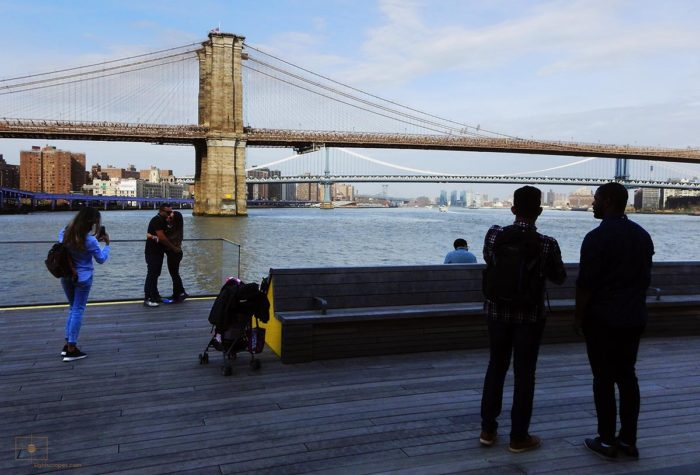 Couple Kissing while Others Look over the East River - South Street Seaport, New York City