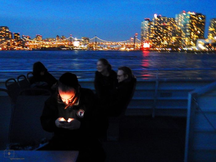 Religious Man Texting at Night on the East River Ferry - East River, New York City