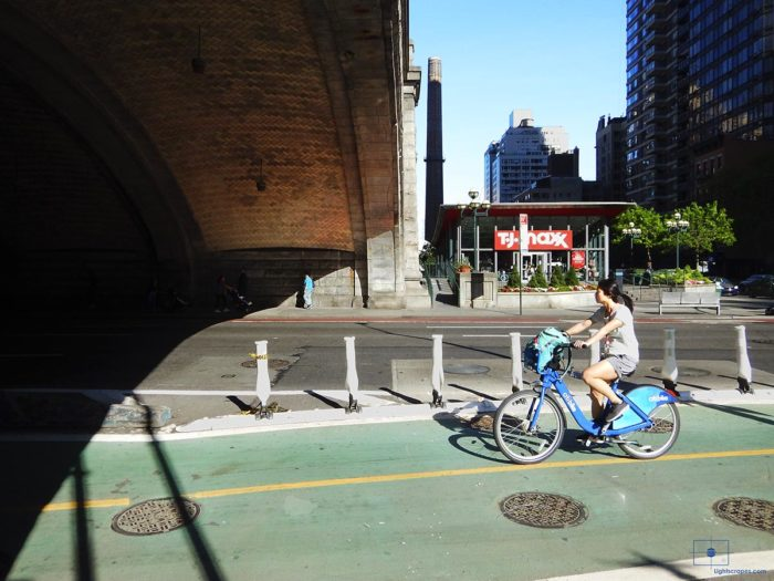 Woman on a Bicycle Riding under the Queensboro Bridge - Manhattan, New York City